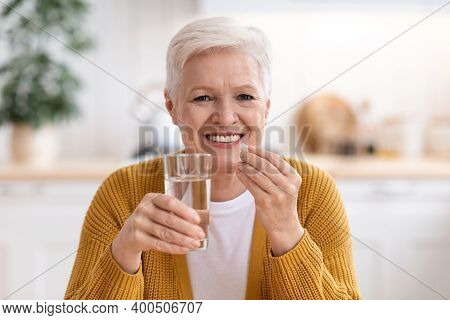 Supplements, Vitamins, Healthy Lifestyle Concept. Closeup Of Happy Senior Lady Holding Glass Of Wate