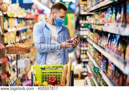 Portrait Of Young Man With Shopping Trolley Cart In Supermarket Buying Groceries Food Walking Along