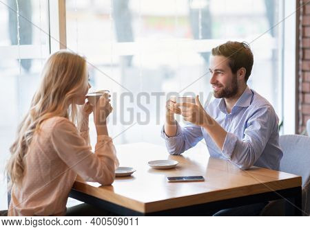 Portrait Of Lovely Romantic Couple Sitting In Urban Cafe With Fresh Coffee, Enjoying Their Date, Hav