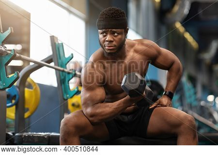 Concentrated African American Muscular Shirtless Guy Bodybuilder Exercising With Barbell At Gym, Sit
