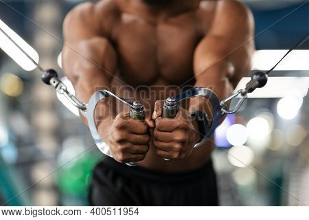 Unrecognizable Black Man Bodybuilder Training Triceps On Crossover Exerciser In Gym, Cropped. Shirtl
