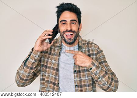 Handsome hispanic man with beard having conversation talking on the smartphone smiling and laughing hard out loud because funny crazy joke.