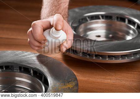Man Spraying Anti Rust Inhibitor On A Brake Rotor