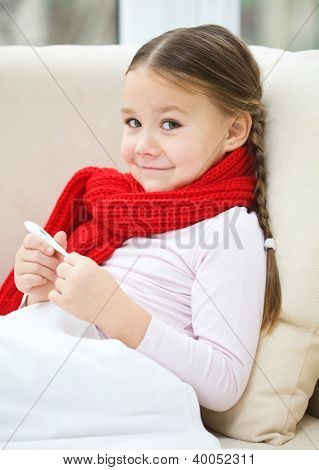 Ill little girl is reading thermometer while laying on sofa
