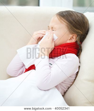 Little girl is blowing her nose while sitting on a sofa
