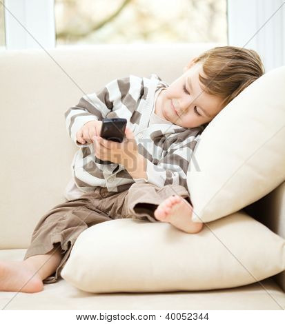Little boy is watching tv while sitting on a couch