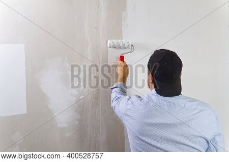 Painting A Drywall By Painting Roller And White Latex Color.