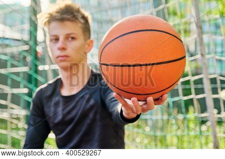 Close-up Basketball Ball In The Hand Of Teenage Guy, Outdoor Basketball City Court Background. Activ