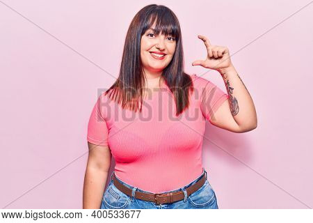 Young plus size woman wearing casual clothes smiling and confident gesturing with hand doing small size sign with fingers looking and the camera. measure concept.