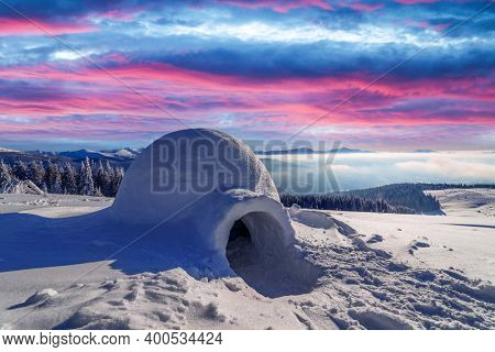 Real snow igloo house in the winter mountains glowing by morning sunlight. Incredible purple sunset with glowing clouds on the background. Winter holiday concept