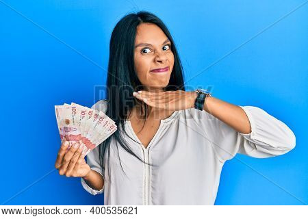 Young african american woman holding 10 colombian pesos banknotes cutting throat with hand as knife, threaten aggression with furious violence