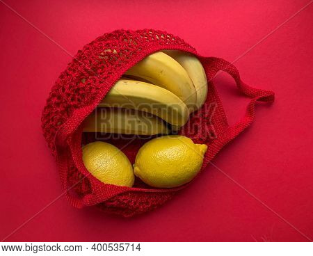 String Bag With Fruit. Bananas And Lemons In A Red String Bag On A Red Background, Photo From Above.