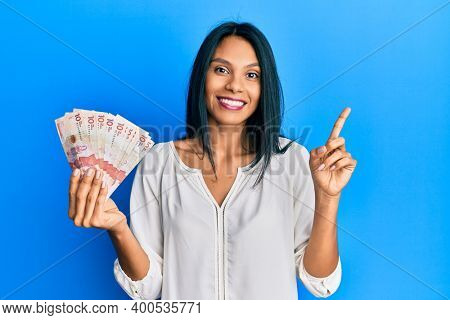 Young african american woman holding 10 colombian pesos banknotes cheerful with a smile on face pointing with hand and finger up to the side with happy and natural expression
