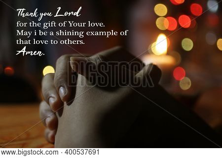 Prayer Hands On The Table With Candle And Colorful Christmas Lights Background. Thank You Lord For T