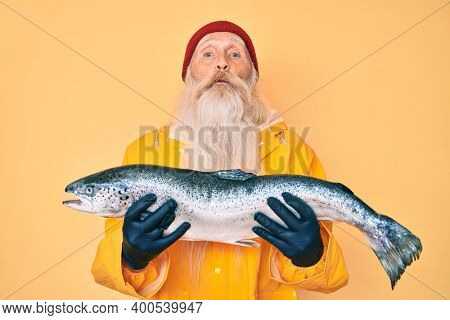 Old senior man with grey hair and long beard wearing raincoat holding fresh salmon puffing cheeks with funny face. mouth inflated with air, catching air.