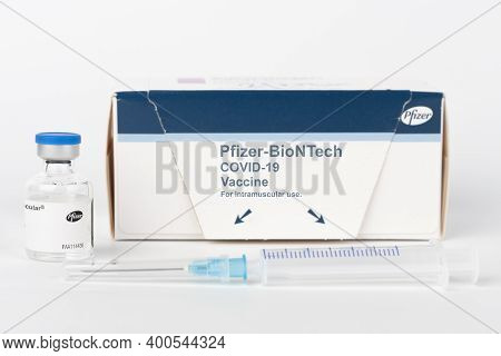 Brnenec, Czech Republic - December 12, 2020:  Syringe with needle, vial and paper box with Covid-19 vaccines. Pharmaceutical corporation Pfizer with  BioNTech devoleped a vaccine on Covid-19.