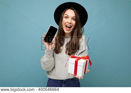 Photo Shot Of Charming Happy Joyful Young Brunette Woman Isolated Over Blue Background Wall Wearing