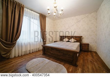 Luxury Empty Bedroom At Home Flat Or Hotel. Wooden Floor Walls. Lighting Equipment Hanging On Ceilin