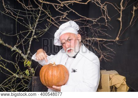 Big Pumpkin For Halloween. Bearded Chef With Pumpkin. Diet Food. Chef Man In White Apron Presenting