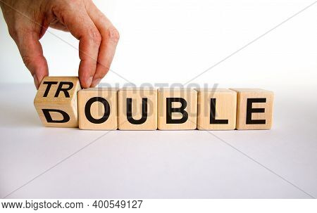 Double Trouble Symbol. Male Hand Flips A Wooden Cube With Words 'double Trouble'. Beautiful White Ba