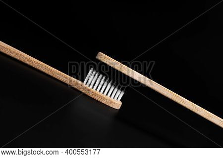 Two Eco-friendly Antibacterial Bamboo Wood Toothbrushes With White And Black Bristles On A Black Bac