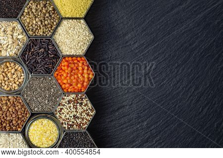 Food Background Of Various Cereals And Grains In Hexagonal Shaped Honeycomb Jars