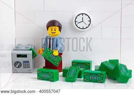 Tambov, Russian Federation - December 22, 2020 Lego Businessperson Minifigure Putting Money Into A S