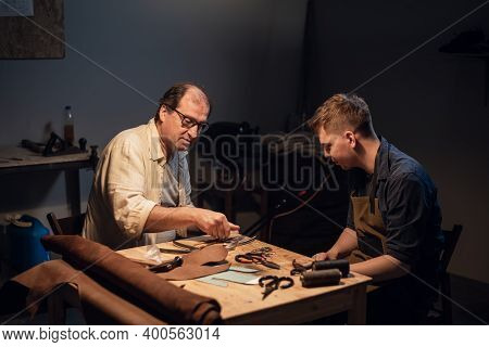 An Elderly Shoemaker And His Apprentice Create Shoes By Hand In Their Workshop With Various Tools