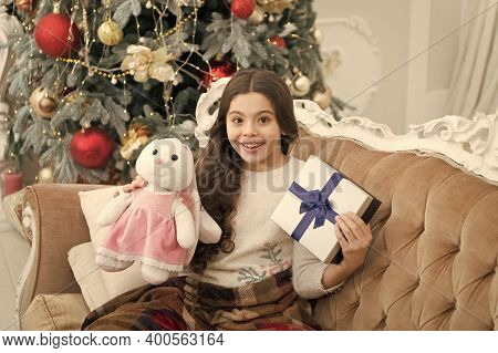 Adorable Girl Play With Toy In Christmas Eve. Present Concept. Smiling Child Enjoy Winter Holidays.