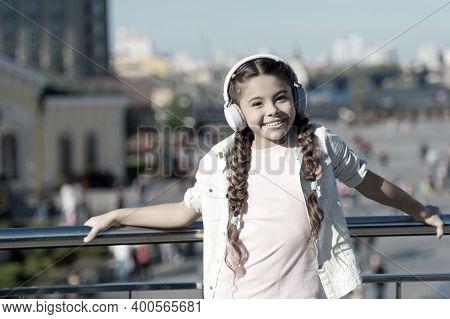 The World Beyond My Headphones Is Too Chaotic. Little Girl Wearing Headphones On Urban Outdoor. Cute