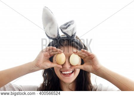 Happy Easter! Happy Young Woman In Bunny Ears And Linen Dress Holding Easter Eggs At Eyes And Smilin