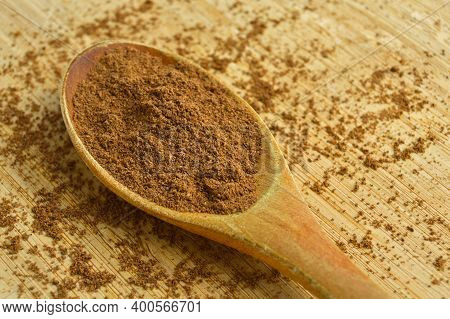 Powdered Spices Allspice In Wooden Spoon, Bamboo On Cutting Board