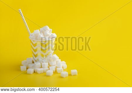 Straw In Disposable Paper Cup Filled With Sugar Cubes Among Heap Of Sugar Cubes Over Yellow Backgrou
