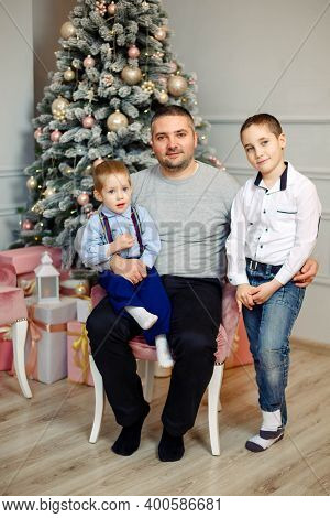 Young Family Enjoying Their Holiday Time Together. Happy Holidays. Smiling Father And Sons Celebrati