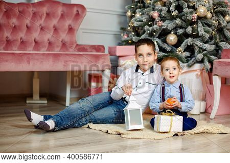 Cute Little Children With Christmas Gift Boxes Sitting Near Christmas Tree At Home. Funny Kids Lying