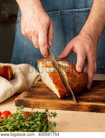 Faceless Man Cutting Fresh Home Baked Crusty Bread With Large Knife On Wooden Board On Kitchen Table