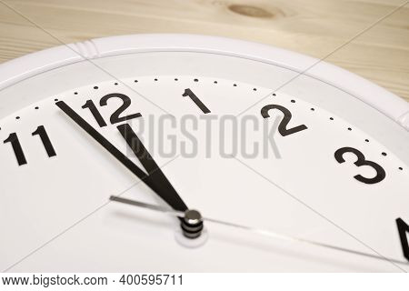 Dial Of An Analog Clock Close Up On A Wooden Background. The Time Is 23:59. White Dial, Black Numera