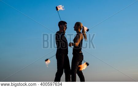 Rhythmical Swinging. Couple Of Dancers Swing Burning Poi Blue Sky. Fiery Poi Swinging. Fire Performa
