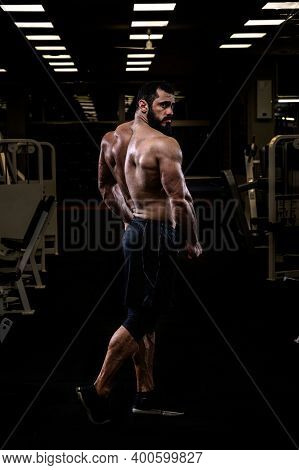 Strong Young Bearded Caucasian Man With Sport Physique Body Standing In Dark Fitness Gym Showing Pow