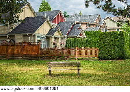 Old Wooden Bench In A Park Are In Front Of Residential Houses
