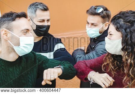 Young Friends Greet Each Other Using Their Elbow Wearing Surgical Masks - Social Distancing And Coro