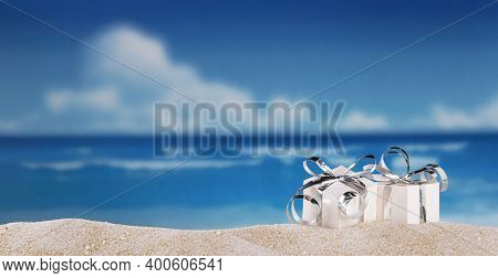 Gifts With Silver Ribbon In The Sand On Beach On A Sunny Day