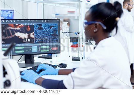 Back View Of African Researcher Working On Computer In Modern Faciliy. Multiethnic Healthcare Scient