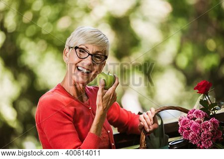 Healthy Looking Senior Woman With Grey Hair Holding Apple Outside In The Park