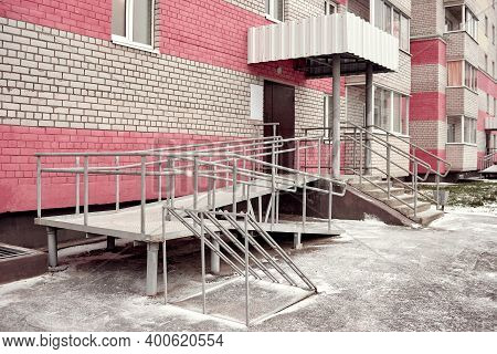 Ramp For Baby Strollers And Wheelchairs With Metal Handrails At The Entrance To The Residential Buil