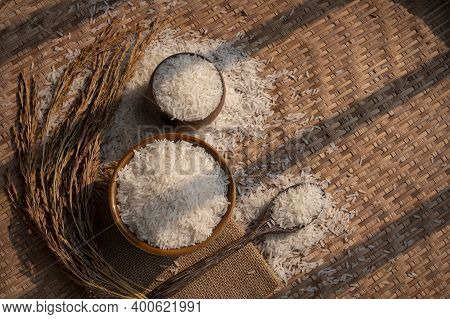 Sunlight And Shadow On Surface Of White Rice (thai Jasmine Rice) In Ceramic Bowl And Wooden Spoon Wi
