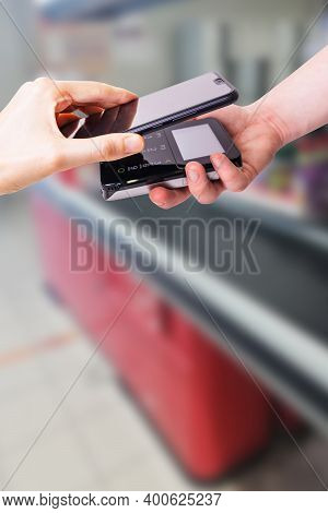Pos Terminals And Smartphone. In The Background Is A Supermarket Checkout. Banking Equipment. Acquir