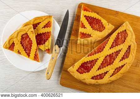 Two Pieces Of Wicker Shortcrust Pie With Apricot Jam, Kitchen Knife In White Plate, Sweet Pie On Bam