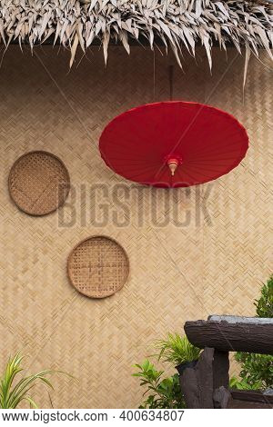 Red Paper Umbrella With 2 Threshing Basket On Bamboo Weave Wall Of Traditional Hut With Blurred Gree