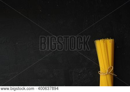 Flat Lay Of Spaghetti For Cooking Italian Pasta Over Black Background. Top View Of Traditional Itali
